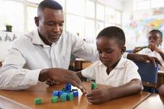 Professeur aidant l'écolier élémentaire comptant avec des blocs Photo libre de droits