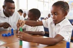 Professeur aidant l'écolier élémentaire comptant avec des blocs Photos libres de droits