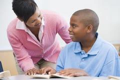 Professeur aidant la pupille d'école primaire photographie stock libre de droits