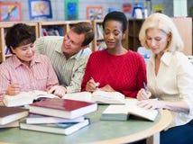 Professeur aidant les étudiants mûrs dans la bibliothèque Image libre de droits