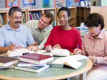 Professeur aidant les étudiants mûrs dans la bibliothèque photo libre de droits