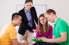Professeur aidant ses étudiants avec le travail Photographie stock