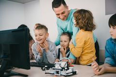 professeur aidant ses étudiants de l'adolescence avec le robot diy sur la tige photographie stock libre de droits
