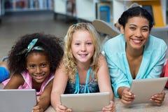 Professeur avec des filles à l'aide des comprimés numériques dans la bibliothèque Photos libres de droits