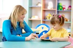 Professeur avec l'enfant dans l'école maternelle Images libres de droits