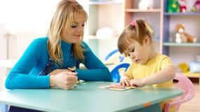 Professeur avec l'enfant dans l'école maternelle image stock