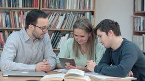 Professeur avec le groupe d'étudiants travaillant au comprimé numérique dans la bibliothèque Image libre de droits