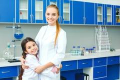 Professeur avec le petit enfant dans étreindre de laboratoire d'école photo libre de droits