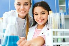 Professeur avec le petit enfant dans l'ampoule de laboratoire d'école avec le liquide image stock