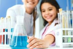 Professeur avec le petit enfant dans l'ampoule de laboratoire d'école avec le plan rapproché liquide image libre de droits