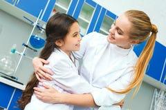 Professeur avec le petit enfant dans le laboratoire d'école regardant sur l'un l'autre photos stock