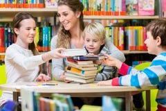 Professeur avec sa classe visitant les livres de lecture de bibliothèque image stock