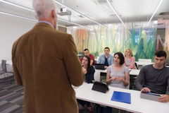 Professeur avec un groupe d'étudiants dans la salle de classe Photos stock