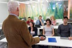 Professeur avec un groupe d'étudiants dans la salle de classe Photographie stock libre de droits