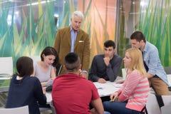 Professeur avec un groupe d'étudiants dans la salle de classe Photo stock