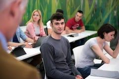 Professeur avec un groupe d'étudiants dans la salle de classe Image stock