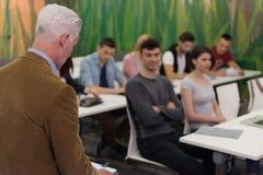 Professeur avec un groupe d'étudiants de lycée dans la salle de classe Images libres de droits
