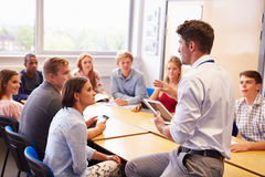 Professeur With College Students donnant la leçon dans la salle de classe Photos libres de droits