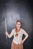 Professeur criard fâché avec l'indicateur sur le backgroun de tableau Photo stock