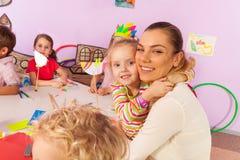 Professeur d'étreinte de petite fille dans la classe de jardin d'enfants Photos libres de droits
