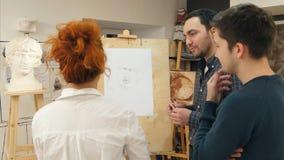 Professeur d'art expliquant deux étudiants masculins comment dessiner la fonte de plâtre Photographie stock