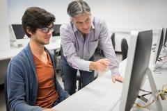 Professeur d'ordinateur aidant un étudiant image libre de droits