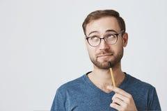 Professeur d'Université barbu songeur dans les lunettes avec des regards intelligents d'expression pensivement de côté, essais po images stock