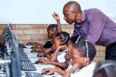 Professeur dans la salle de classe montrant à enfants des qualifications d'ordinateur images stock