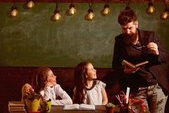 Professeur de écoute d'enfants gais curieux avec l'attention Élèves de professeur et de filles dans la salle de classe, tableau d photo stock