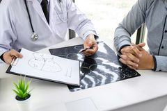 Professeur Doctor ayant la conversation avec le patient et tenant le film radiographique tout en discutant expliquant des symptôm images stock