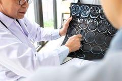 Professeur Doctor ayant la conversation avec le patient et tenant x image stock