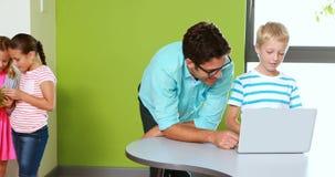 Professeur et écolier à l'aide de l'ordinateur portable dans la salle de classe banque de vidéos