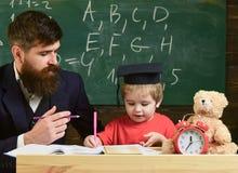 Professeur et élève dans la taloche, tableau sur le fond L'enfant étudie avec le professeur, écoutant avec l'attention images libres de droits