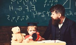 Professeur et élève s'asseyant dans la salle de classe L'homme adulte dans le costume futé regarde au côté tandis que l'enfant jo photographie stock