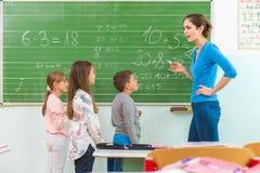 Professeur et étudiant au tableau noir, classe de maths Photographie stock
