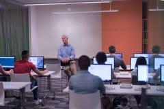 Professeur et étudiants dans la salle de classe de laboratoire d'ordinateur Image stock