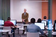 Professeur et étudiants dans la salle de classe de laboratoire d'ordinateur Photo libre de droits