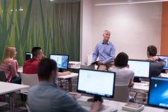 Professeur et étudiants dans la salle de classe de laboratoire d'ordinateur Image libre de droits