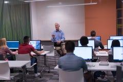 Professeur et étudiants dans la salle de classe de laboratoire d'ordinateur Photographie stock libre de droits