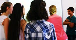 Professeur et étudiants discutant au-dessus de la carte du monde sur le tableau blanc dans la salle de classe banque de vidéos