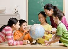 Professeur et étudiants visualisant le globe dans la salle de classe Photographie stock