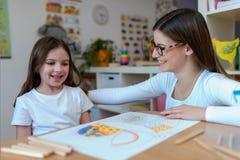 Professeur et enfant ayant l'amusement et le temps créatif ensemble Photographie stock libre de droits