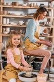professeur et enfant faisant les pots en céramique sur des roues de poterie photo libre de droits