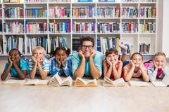 Professeur et enfants se trouvant sur le plancher dans la bibliothèque Image libre de droits