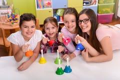 Professeur et enfants tenant la main Bells musicale Photographie stock libre de droits