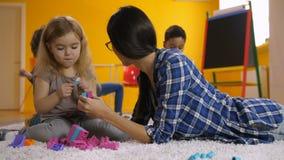 Professeur et fille mignonne communiquant dans le jardin d'enfants clips vidéos