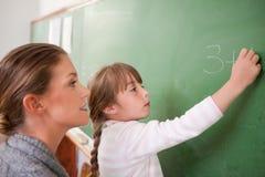 Professeur et un élève faisant une addition images stock