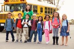 Professeur et un groupe d'enfants d'école primaire à un arrêt d'autobus photos stock