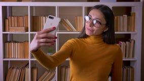 Professeur f?minin de belle brune en verres faisant les selfies dr?les sur la langue d'apparence de smartphone joyeux ? la biblio banque de vidéos