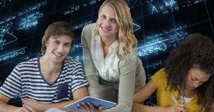 Professeur féminin tenant la tablette par des étudiants contre des équations de maths photographie stock